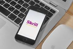 IPhone 5s con Skrill app - sistema de pago electrónico Foto de archivo libre de regalías