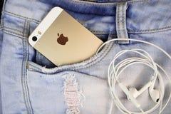 IPhone 5s del oro de Apple en un bolsillo azul del dril de algodón imágenes de archivo libres de regalías
