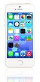 IPhone 5s del oro que muestra la pantalla de inicio con iOS7 Foto de archivo