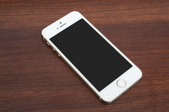 IPhone 5s Gold on wooden background Royalty Free Stock Photo