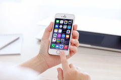 IPhone 5S med IOS 8 i en hand på bakgrund av MacBook Royaltyfria Foton