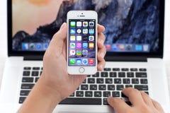 IPhone 5S med IOS 8 i hand över MacBook Pro Royaltyfri Bild