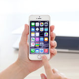 IPhone 5S met IOS 8 in een hand op achtergrond van MacBook Royalty-vrije Stock Foto