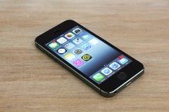 IPhone 5s que miente en una tabla Foto de archivo libre de regalías