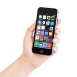 IPhone 5S som för Apple utrymmegrå färger visar iOS 8 i den kvinnliga handen, desi Arkivbilder