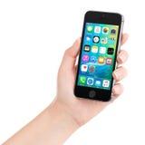 IPhone 5S som för Apple utrymmegrå färger visar iOS 9 i kvinnlig hand Arkivbilder