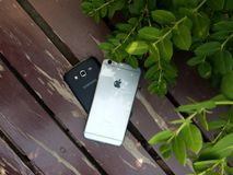 Iphon and Samung mobile rest on Bench Royalty Free Stock Photography
