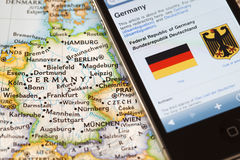 Iphone with tourist application on map of Germany, Europe. Royalty Free Stock Photo