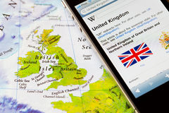 Iphone with travel application on map of United Kingdom Stock Image