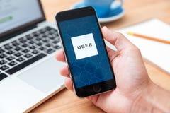 Iphone 6 Uber di mostra app della tenuta dell'uomo Fotografia Stock Libera da Diritti