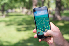 An Iphone user is playing Pokemon. Montreal, CA - July 22, 2016: An Iphone user is playing Pokemon Go, a mobile game developed by Niantic royalty free stock photos