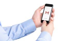 IPhone van Apple van de mensenholding met de toepassingsembleem van Google Gmail Stock Afbeeldingen