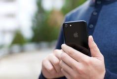 IPhone 7 van de mensenholding Jet Black Onyx Royalty-vrije Stock Afbeeldingen