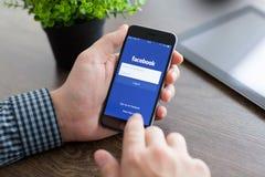 IPhone 6 van de mensenholding met Facebook op het scherm Royalty-vrije Stock Afbeelding