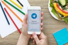 IPhone van de vrouwenholding met het sociale Telegram van de voorzien van een netwerkdienst  Stock Foto's