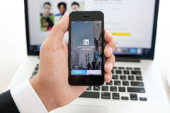 IPhone van de zakenmanholding met app LinkedIn op het scherm op a stock foto