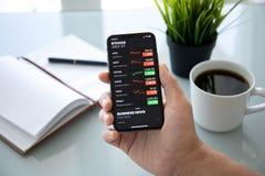 IPhone X van de zakenmanholding met toepassingsvoorraden van Apple royalty-vrije stock afbeeldingen