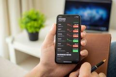 IPhone X van de zakenmanholding met toepassingsvoorraden van Apple royalty-vrije stock fotografie