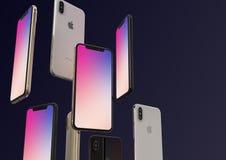IPhone XS金、银和空间灰色智能手机,漂浮在空气,五颜六色的屏幕 免版税库存图片