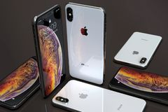 IPhone XS Silver smartphones, arranged in mosaic composition. Smartphones iPhone Xs Silver arranged in mosaic composition, on a dark background. Concept royalty free stock images