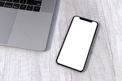 IPhone Xs Silver style smartphone mock-up perspective on table. Smartphone similar to iPhone Xs Silver on a white wood table background, next to a laptop royalty free stock images