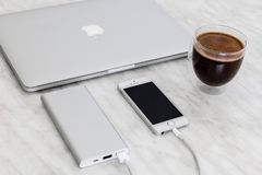 IPhonese die met machtsbank, Macbook en kop belasten van koffie op marmeren achtergrond stock foto's
