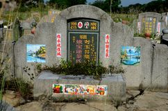 Chinese grave tombstone with photograph and painted artistic tiles Ipoh Malaysia. Ipoh, Malaysia - June 3, 2017: An ornate and decorated Chinese grave at a royalty free stock photos