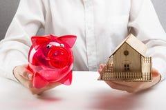 Ipoteca o concetto di risparmio mani che tengono salvadanaio e casa miniatura Fotografia Stock Libera da Diritti