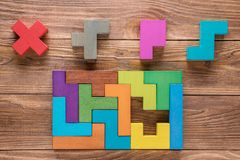 IQ test. Choose correct answer. Logical tasks composed of colorful wooden shapes, top view. Children`s educational logical task,. Flat lay. Visual conundrum stock photo