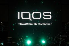 Iqos logo in front of bar terrace in Serbia. Iqos, beloning to Philip Morris International, is a tobacco heating cigarette system stock photography
