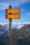 Ir de excursión el poste indicador con las montañas Imagen de archivo