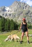 Ir de excursión a la muchacha que presenta con su perro Imagen de archivo