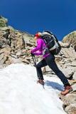 Ir de excursión a la mujer en montañas con nieve Fotos de archivo