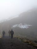 Ir de excursión una montaña en la niebla Fotografía de archivo