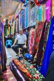 Irański sprzedawcy obsiadanie wśród kolorowych tkanin w tkanina sklepie, Obraz Royalty Free