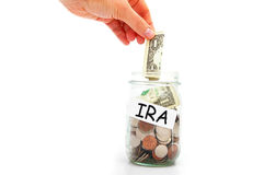 IRA savings. Hand putting a dollar into a IRA coin jar, isolated on white royalty free stock image