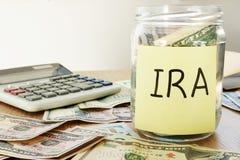 IRA som är skriftlig på en pinne och en krus med dollar royaltyfria bilder