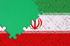 Iran flag is depicted on a completed jigsaw puzzle with free green copy space on the left side.  stock photo