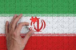 Iran flag is depicted on a puzzle, which the man`s hand completes to fold.  stock image