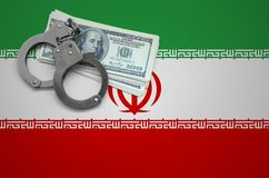 Iran flag with handcuffs and a bundle of dollars. The concept of breaking the law and thieves crimes.  royalty free stock photo