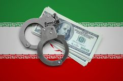 Iran flag with handcuffs and a bundle of dollars. Currency corruption in the country. Financial crimes.  royalty free stock photography