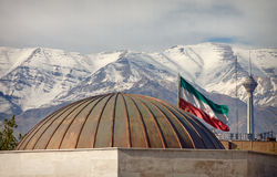 Iran Flag and Milad Tower in Front of Snow Covered Alborz Mountains royalty free stock photo
