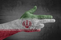 Iran flag painted on male hand like a gun. Isolated on concrete stock photo