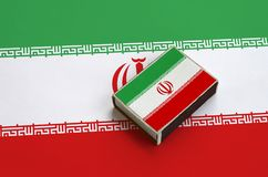 Iran flag is pictured on a matchbox that lies on a large flag.  stock photos