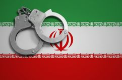 Iran flag and police handcuffs. The concept of crime and offenses in the country.  stock photography