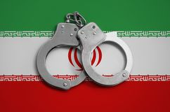 Iran flag and police handcuffs. The concept of observance of the law in the country and protection from crime.  stock photos