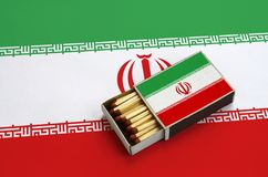 Iran flag is shown in an open matchbox, which is filled with matches and lies on a large flag.  stock photography
