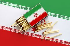 Iran flag is shown on an open matchbox, from which several matches fall and lies on a large flag.  royalty free stock images