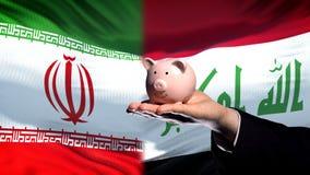 Iran investment in Iraq, businessman hand holding piggybank, flag background. Stock photo stock photography