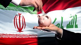 Iran investment in Iraq, hand putting money in piggybank on flag background. Stock photo royalty free stock photography